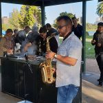 imc emplee plays the saxaphone at a barbeque