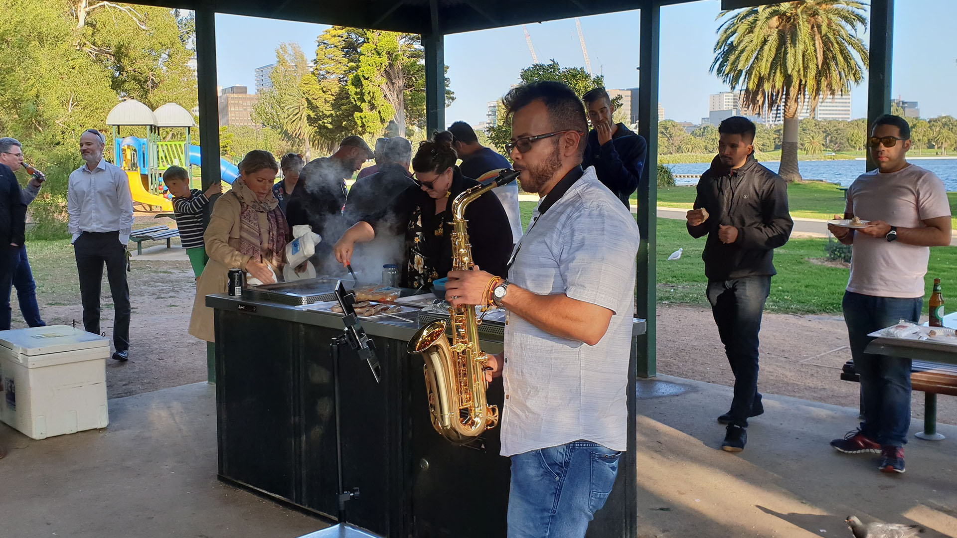 imc employee playing saxaphone at a bbq