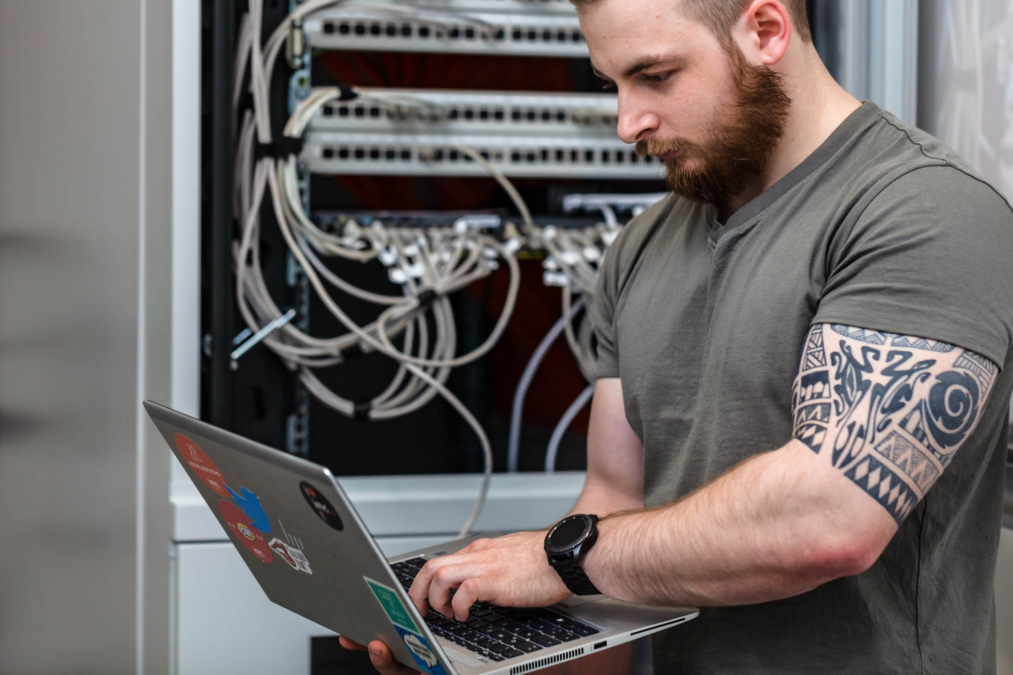 it infrastructure worker on laptop infront of server rack