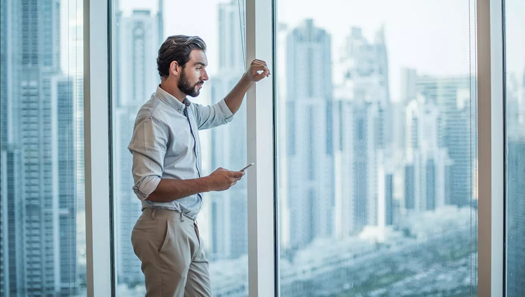 Man looks out from window at city