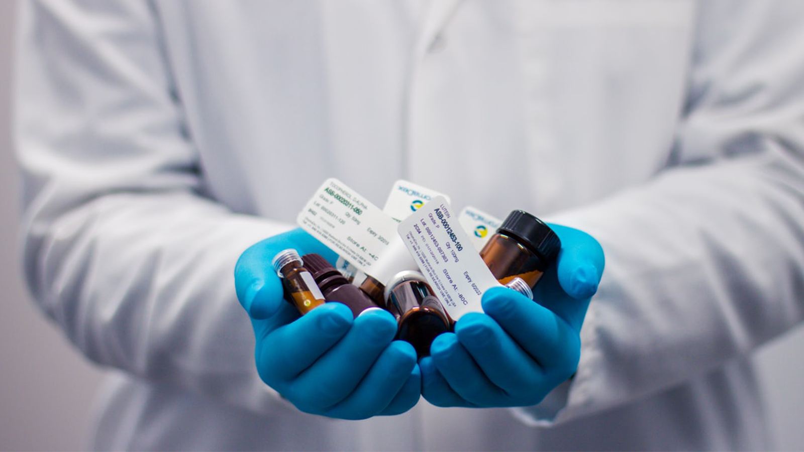 close up of lab technician holding vials in gloved hands
