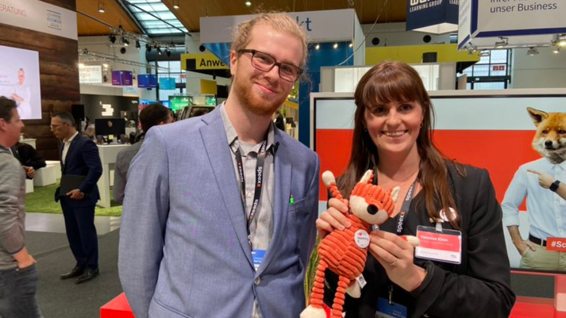imc employees at conference with soft toy