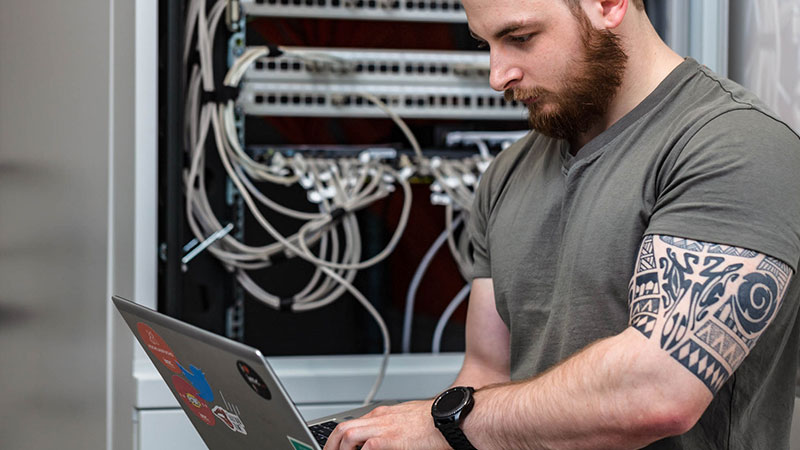 it specialist with laptop infront of server