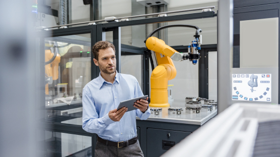 man stands in hi tech manufacturing environment